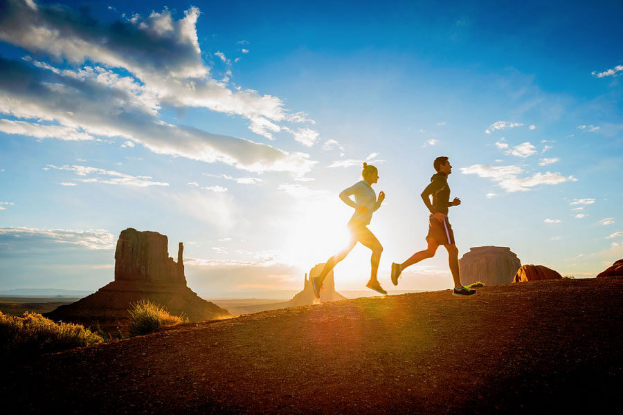 man and woman running with sports headphones