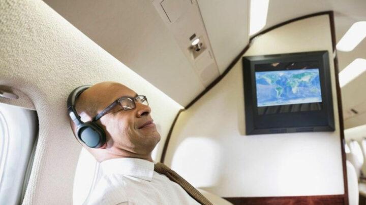 man wearing headphones on plane