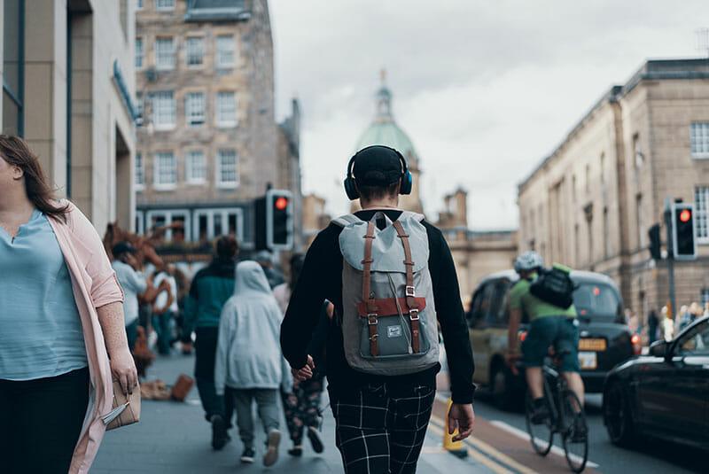 Man with headphones walking on the street.